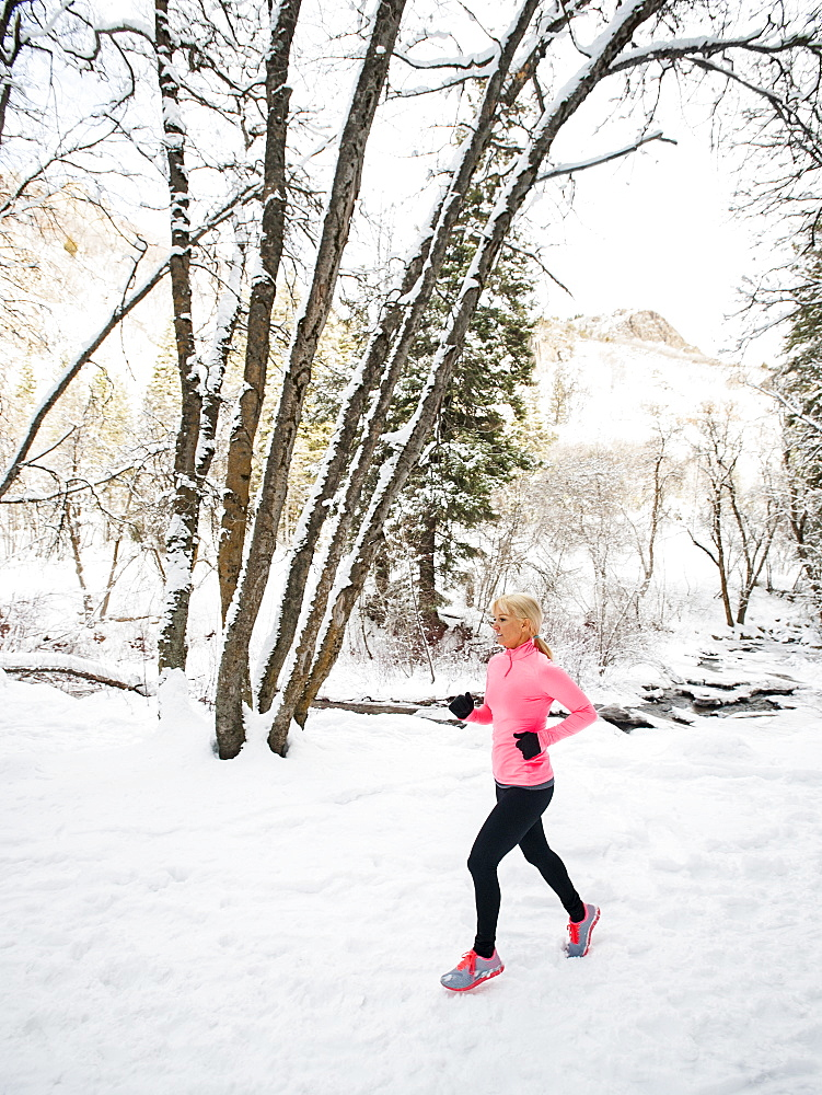 Woman jogging in winter forest, Salt Lake City, Utah USA