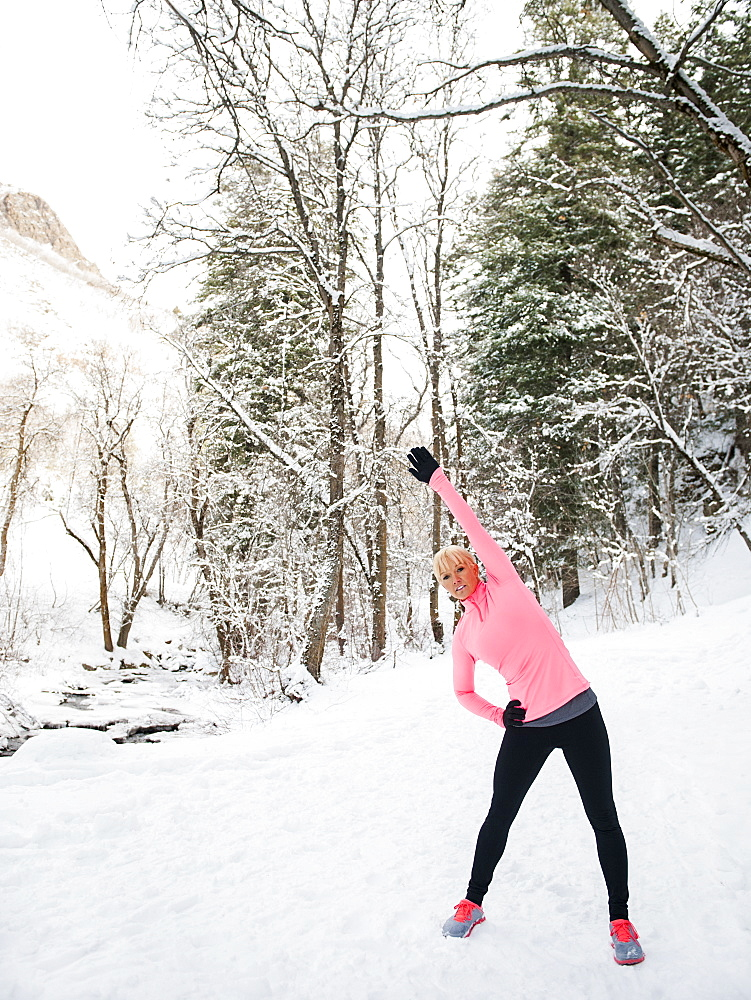 Woman exercising in winter forest, Salt Lake City, Utah USA