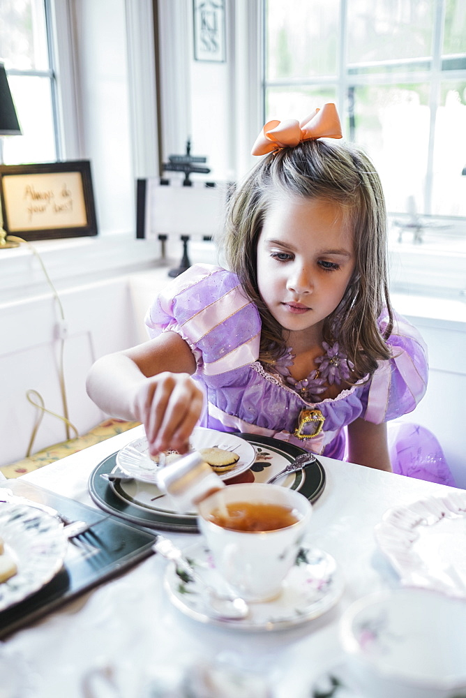 Girl (4-5) eating cookies at dining table