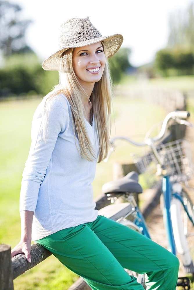 Portrait of smiling woman in straw hat riding bicycle - 1178-23008