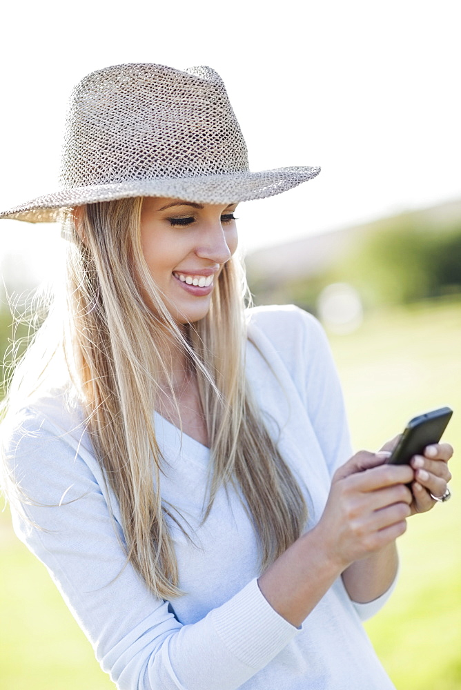 Portrait of smiling woman in straw hat using mobile phone