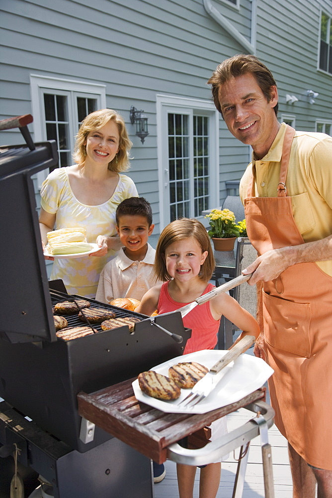 Family barbequing on deck