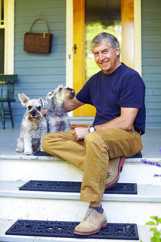 Man with his schnauzers sitting on porch, Albany, New York State, USA