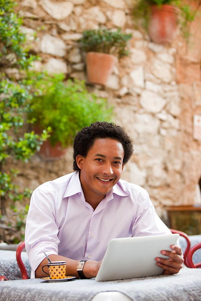 France, Cassis, Man using digital tablet in cafe, France, Cassis