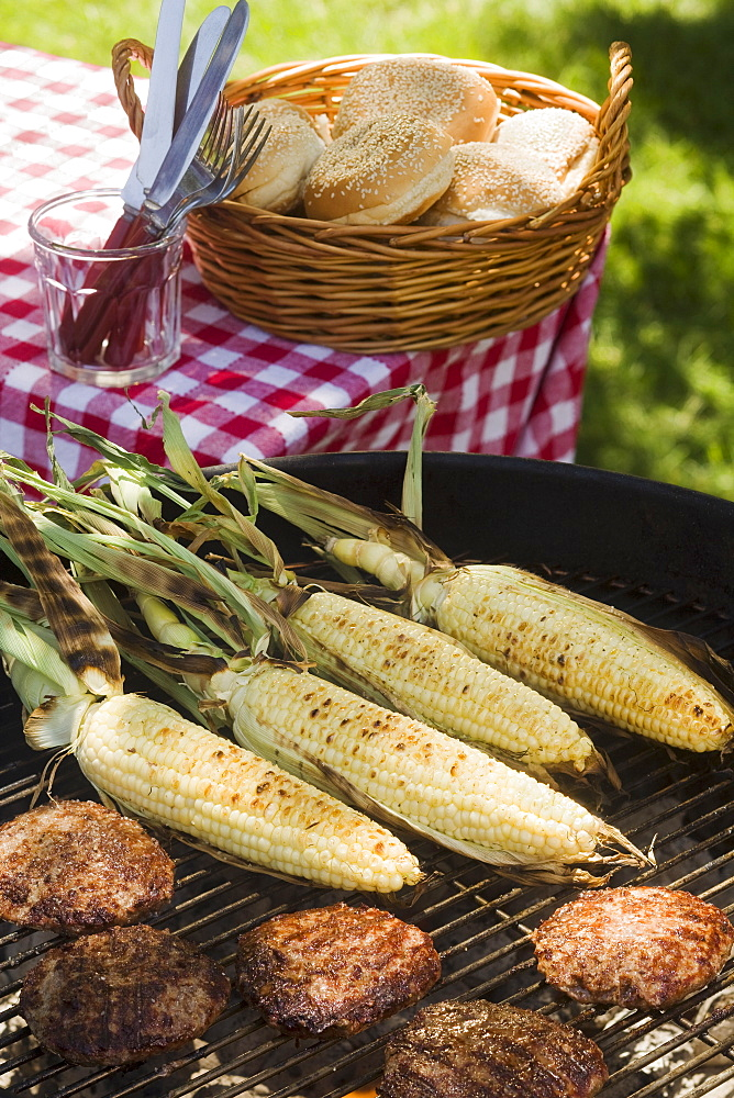 Corn and hamburgers cooking on grill