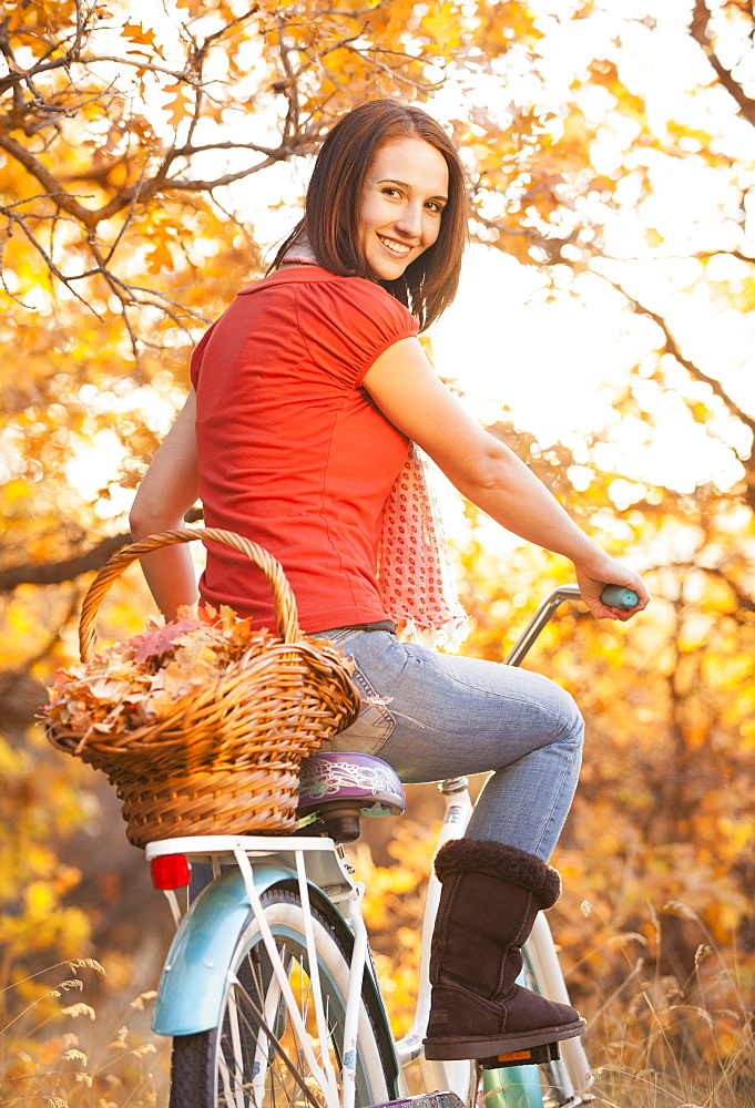 Happy young woman with bicycle in autumn in forest, Alpine, Utah