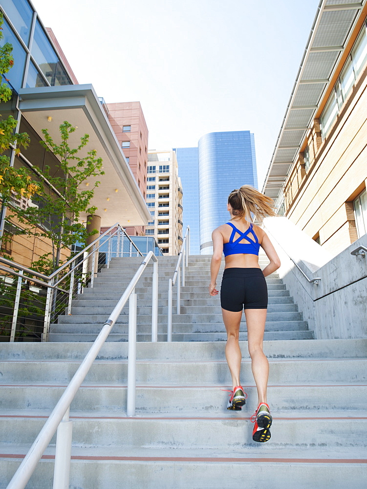 USA, California, Los Angeles, Young woman running on stairs, USA, California, Los Angeles