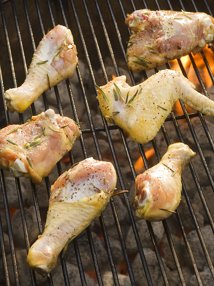 Chicken pieces cooking on grill