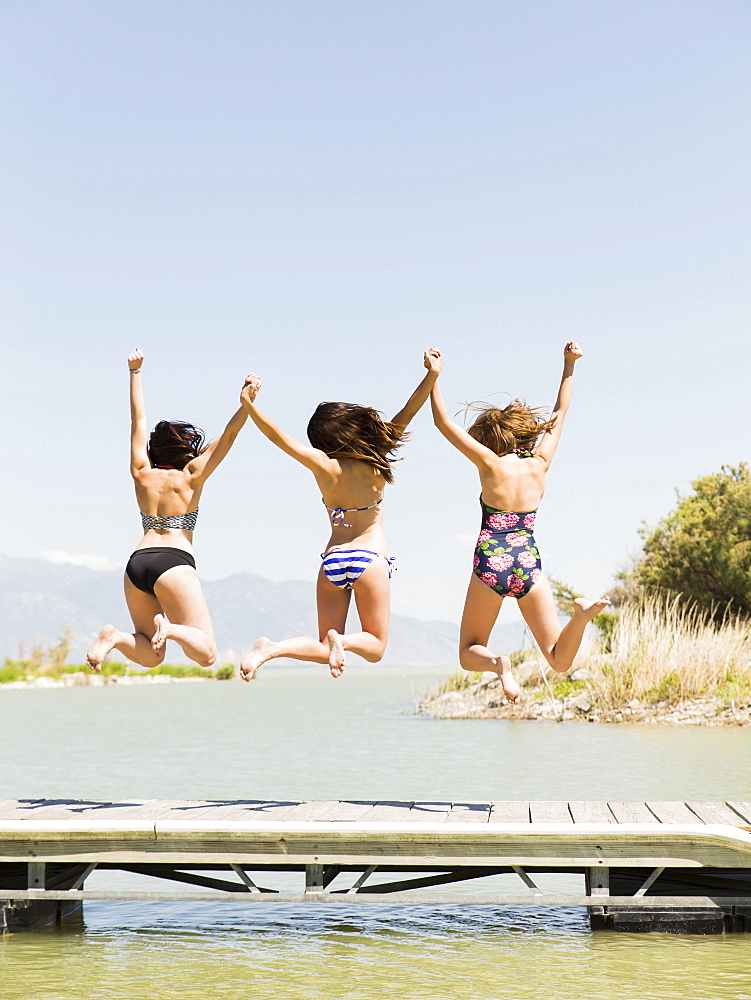 Three women jumping into lake, Salt Lake City, Utah, USA