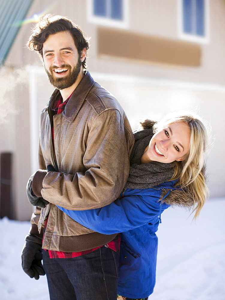 Young woman embracing man in winter, Salt Lake City, Utah