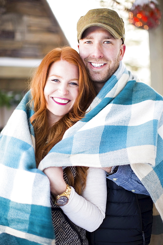 Portrait of mid adult couple wrapped in checked blanket