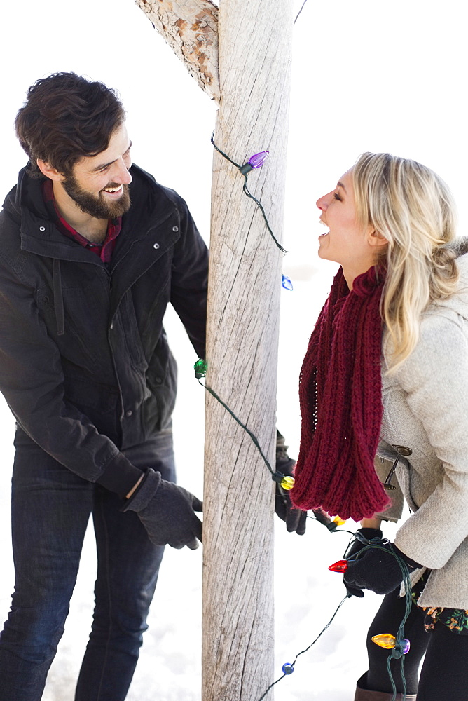 Young couple decorating house with christmas lights