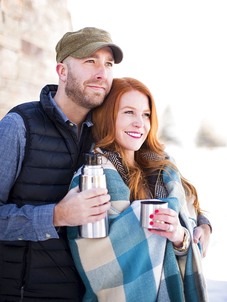 Mid adult couple having drink from vacuum flask, looking away