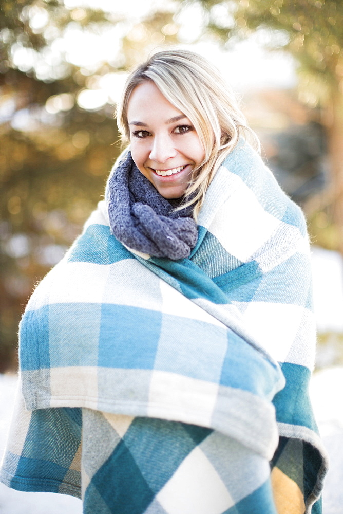 Portrait of woman wrapped in blanket standing outdoors