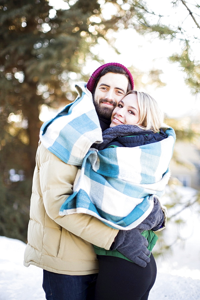 Couple wrapped in blanket hugging outdoors, Salt Lake City, Utah