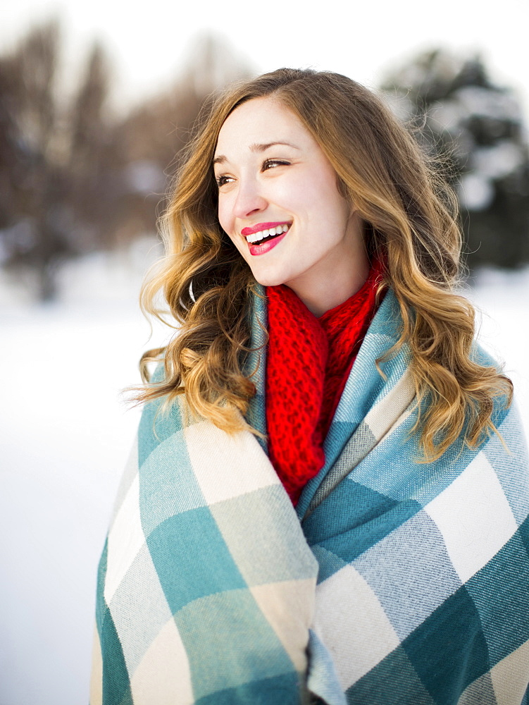 Portrait of woman wrapped in blanket smiling outdoors, Salt Lake City, Utah