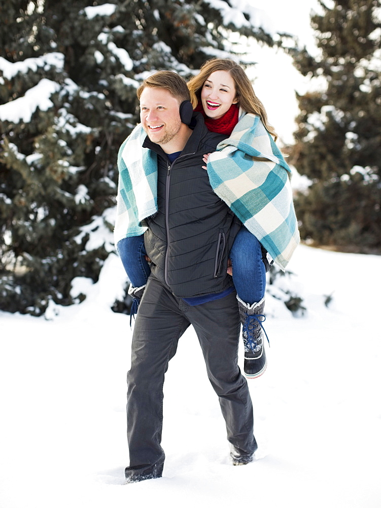 Man giving woman piggyback ride in winter forest, Salt Lake City, Utah
