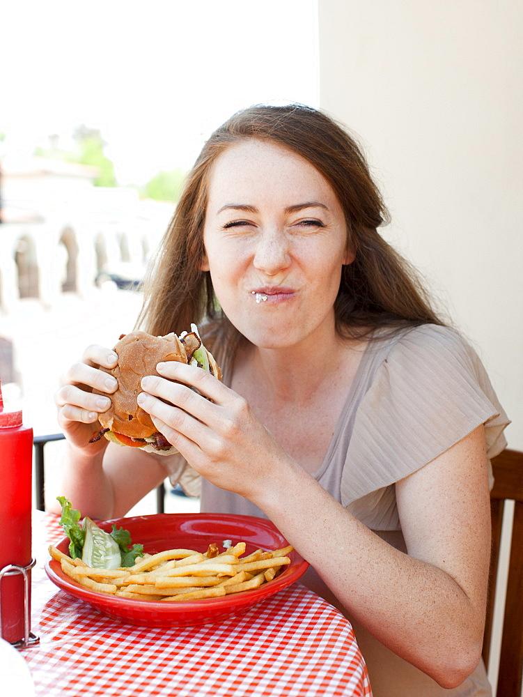Portrait of young woman having burger, USA, Utah, Salt Lake