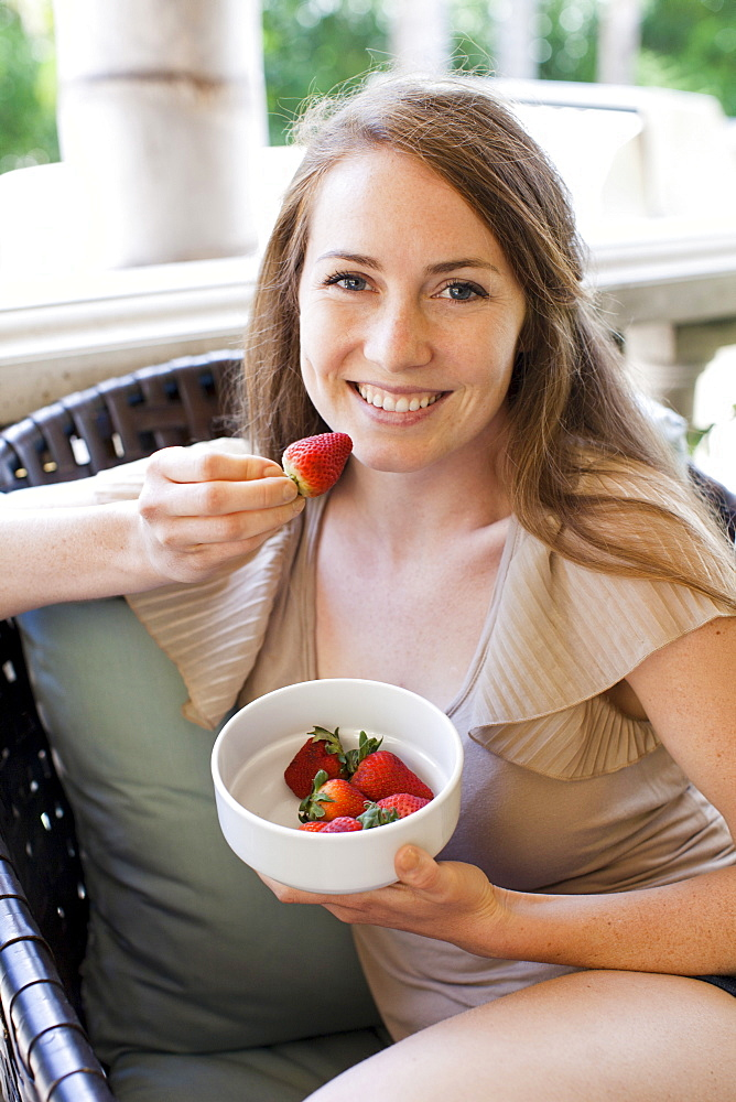 Portrait of young woman having strawberry, USA, Utah, Salt Lake