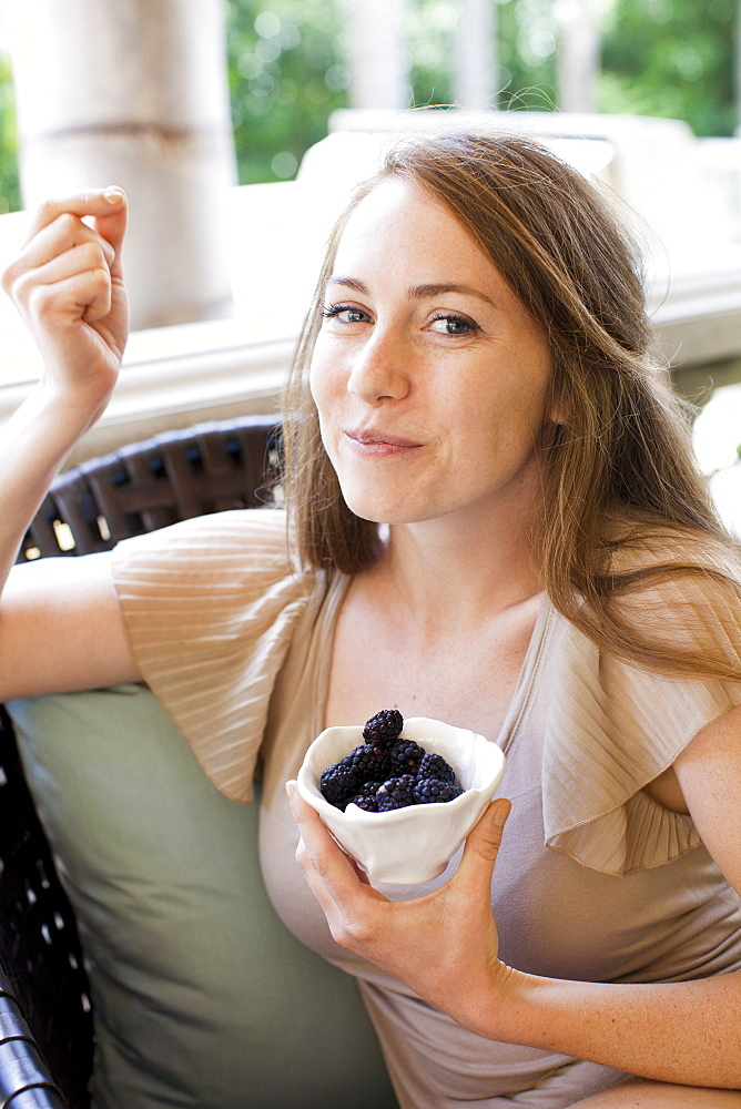 Portrait of young woman having blackberries, USA, Utah, Salt Lake