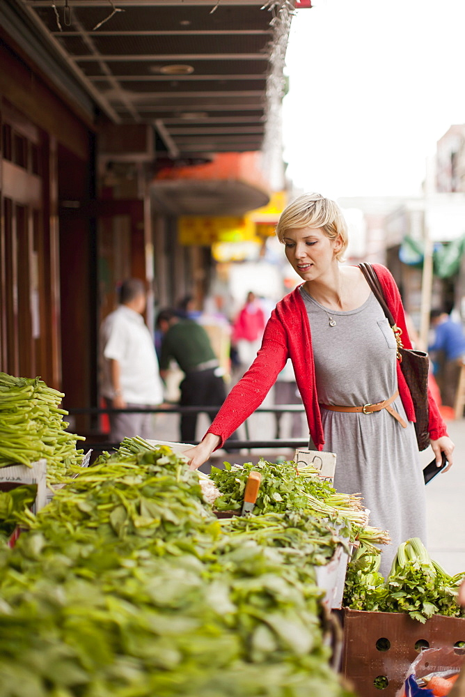 Woman looking at fresh vegetables at street market, USA, New York State, New York