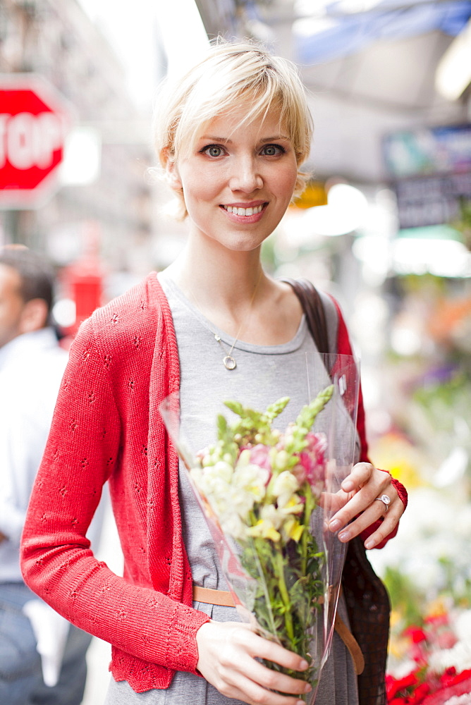 Portrait of smiling woman holding bunch of flowers, USA, New York State, New York