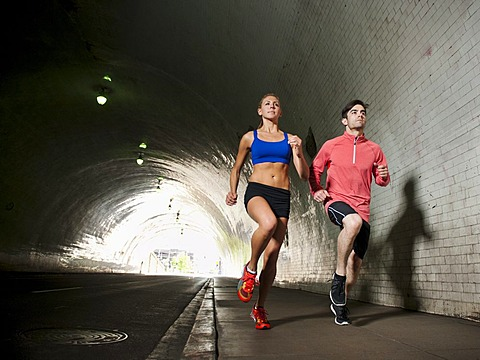 USA, California, Los Angeles, Young man and young woman running in tunnel, USA, California, Los Angeles