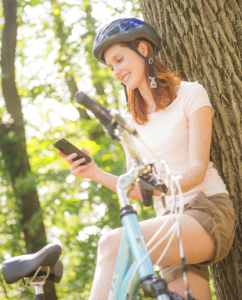 Woman texting on mobile during bicycle trip, USA, New Jersey, Mendham