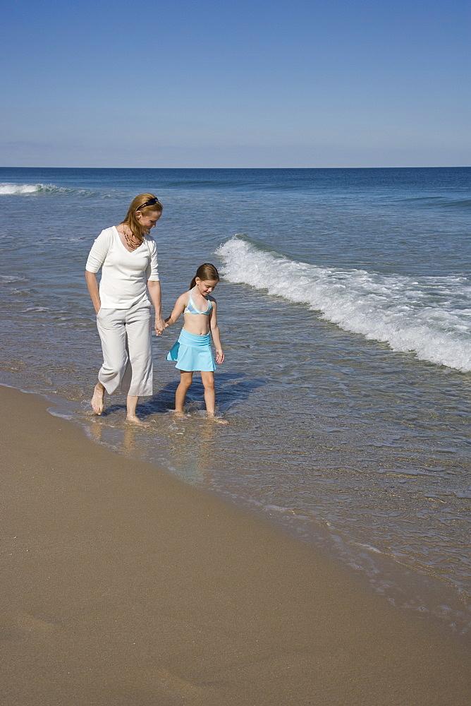 Mother and daughter walking in ocean surf