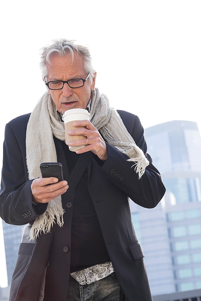 Man in street drinking coffee using smartphone
