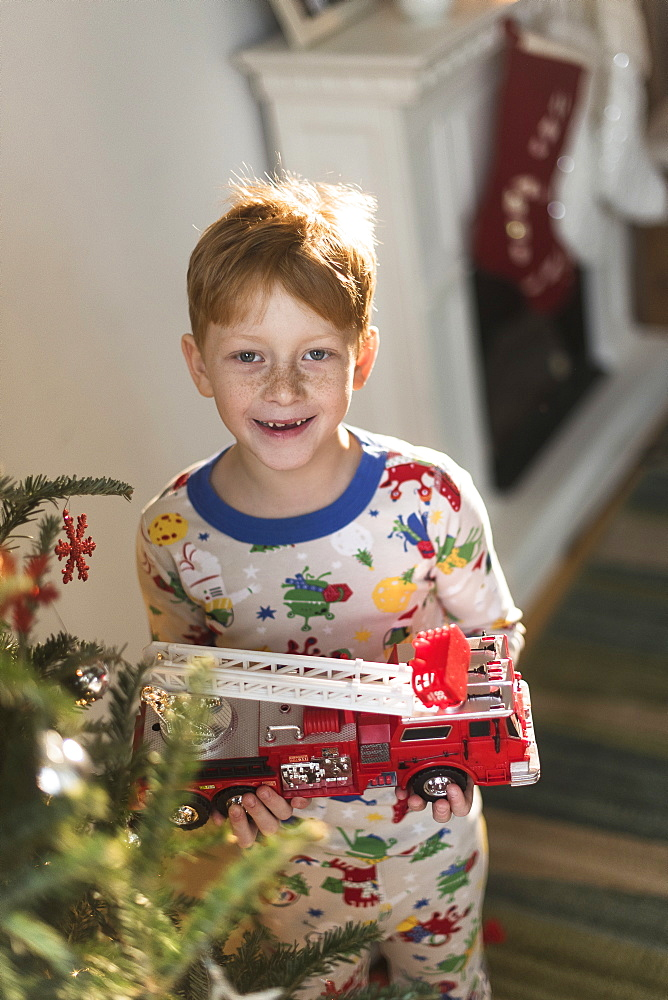 Portrait of boy (6-7) holding toy firetruck