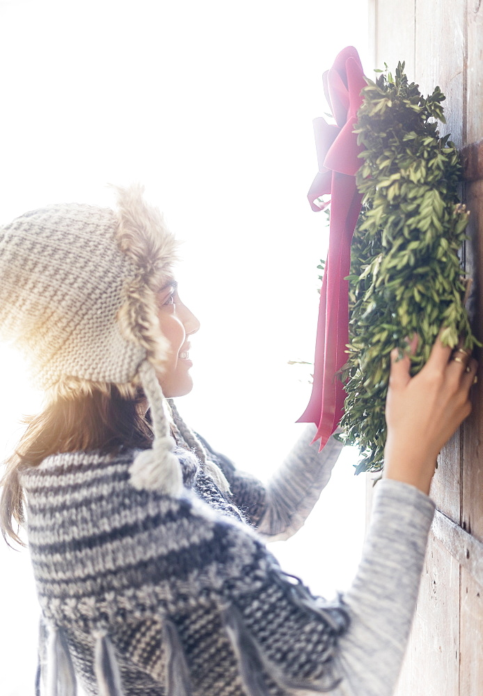 Side view of young woman hanging Christmas wreath on entrance door
