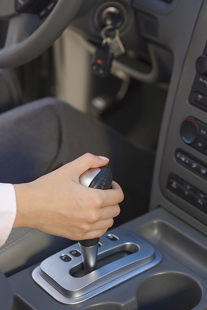 Woman with hand on automatic gearshift in car