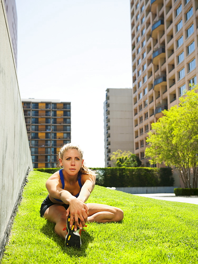 USA, California, Los Angeles, Young woman stretching on grass, USA, California, Los Angeles
