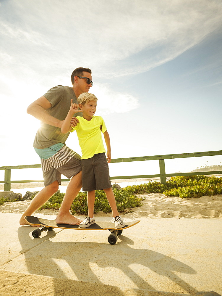 Father skateboarding with his son (6-7), Laguna Beach, California