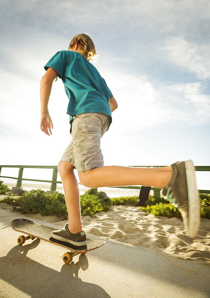 Teenage boy (14-15) skateboarding on path on beach, Laguna Beach, California