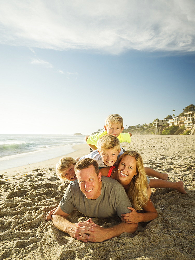 Portrait of smiling family with children (6-7, 10-11, 14-15) on beach, Laguna Beach, California
