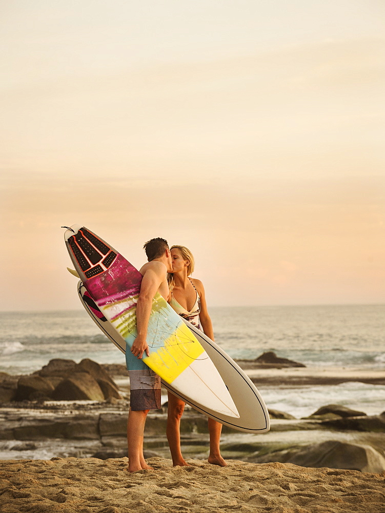 Mid-adult couple kissing on beach at sunset, Laguna Beach, California