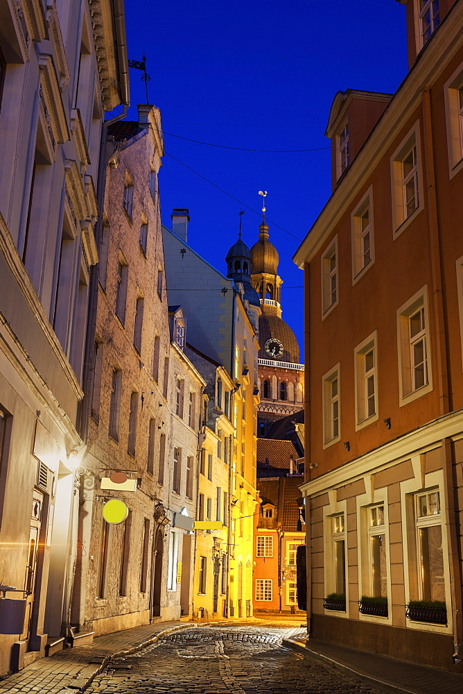 View of illuminated street in old town and Riga Cathedral at dusk, Latvia