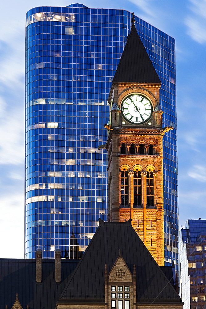 Illuminated clock tower and skyscraper at sunrise, Ontario, Canada