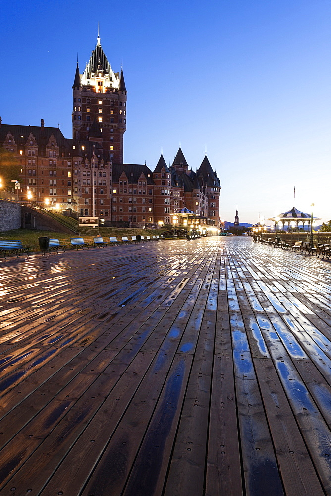 Low angle view of wooden pier and illuminated Chateau Frontenac at dawn, Quebec, Canada
