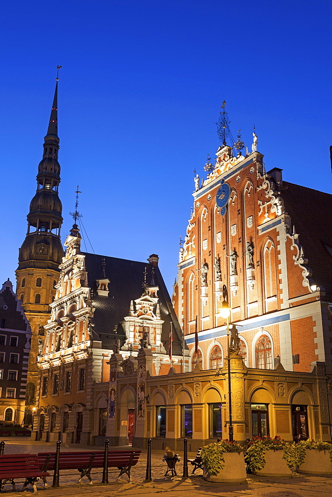 Illuminated House of the Blackheads and St. Peter's Church against blue sky, Latvia