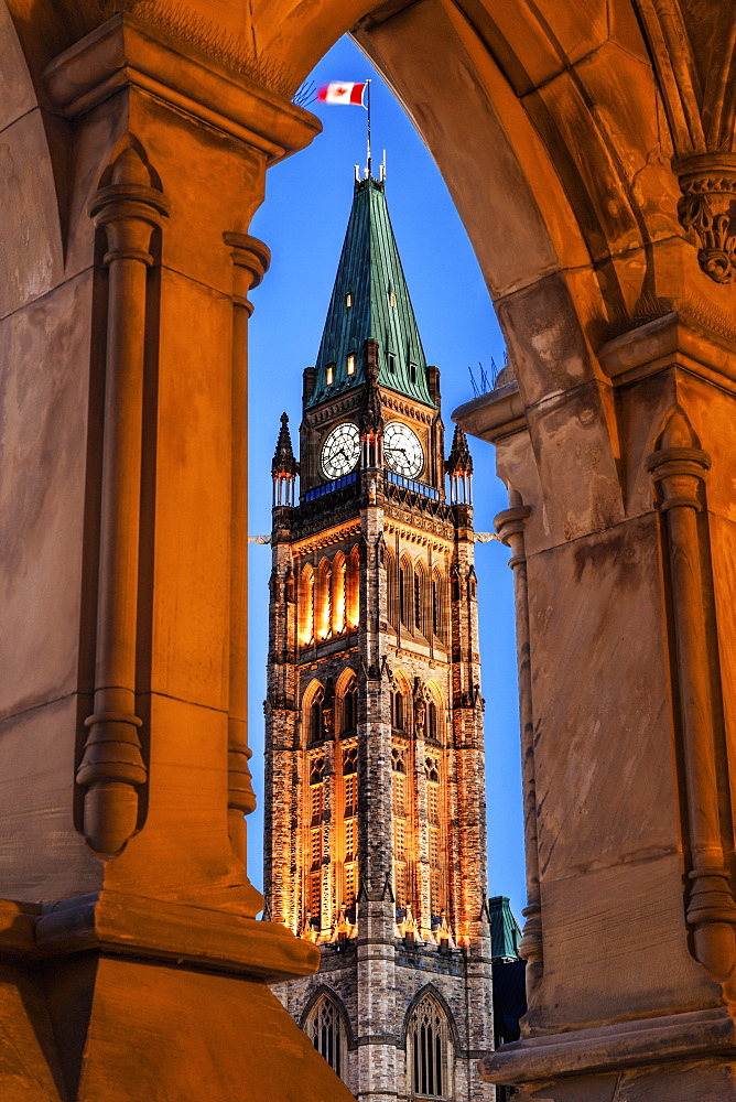 Illuminated Peace Tower seen through lancet arch, Ottawa, Canada