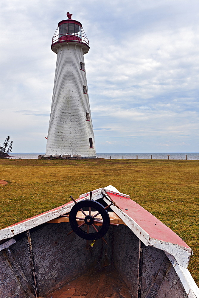 Old rowboat against lighthouse, Prince Edward Island, New Brunswick, Canada