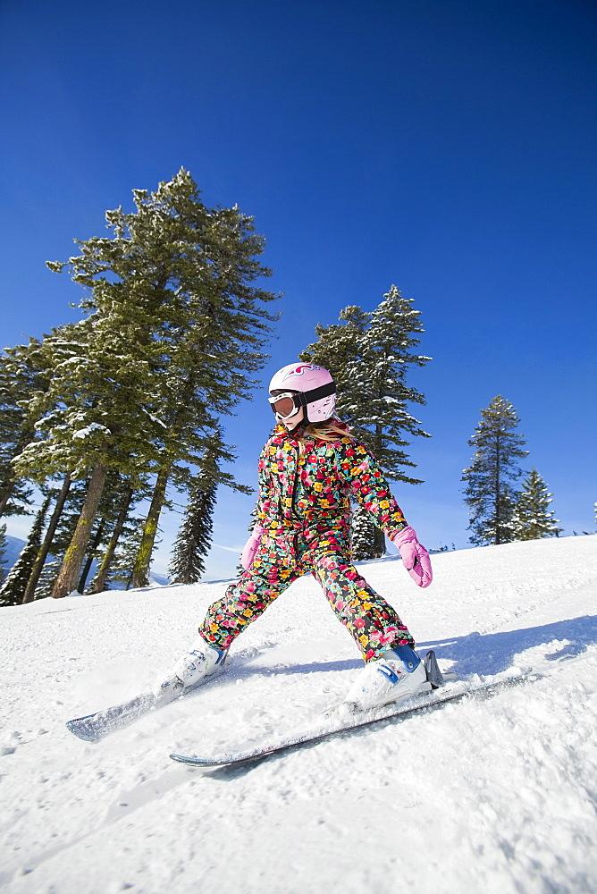 Girl (8-9) skiing in mountains, Whitefish, Montana, USA