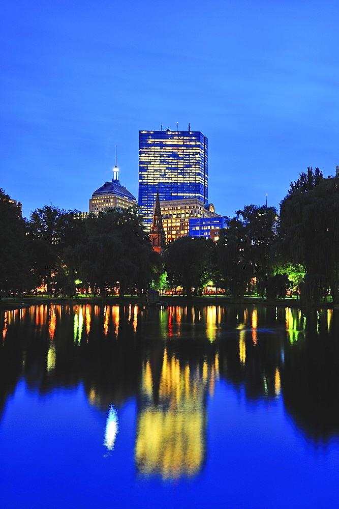 Office building reflecting in pond in Public Gardens at dusk, Boston, Massachusetts