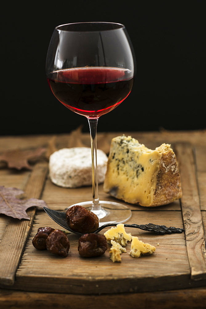 Still life with cheese and red wine on wooden table, studio shot