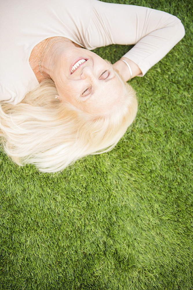 Senior woman lying on grass