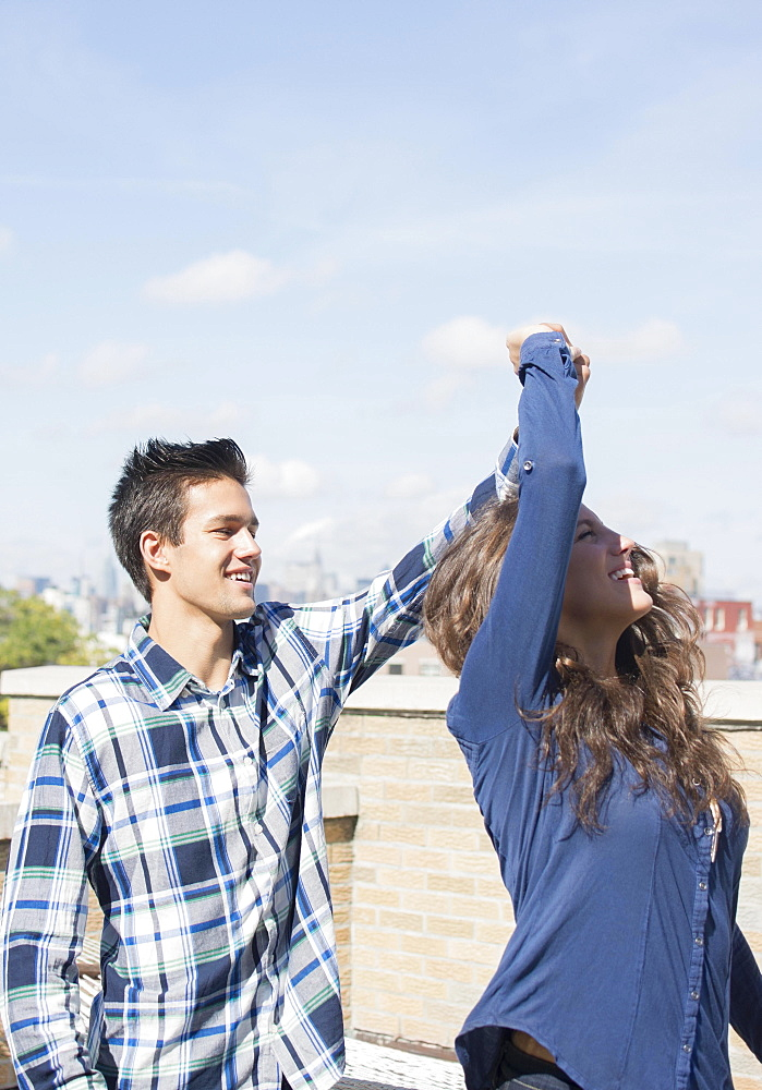 Young couple dancing on roof, Brooklyn, New York