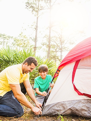 Father and son (12-13) setting up tent, Jupiter, Florida